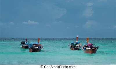 Four long-tailed boat swinging in blue waves, white sail boat on the horizon, Koh Lipe Thailand