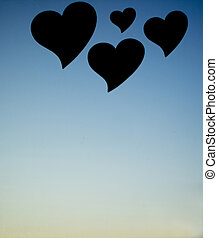 Four love hearts in silhouette with sunset sky background