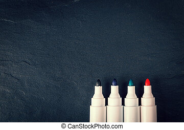 four markers on black background, vintage color tone
