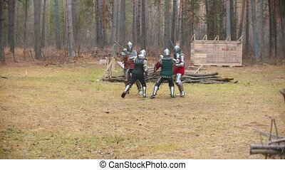 Four men knightes having a fight on the field in the middle of the forest