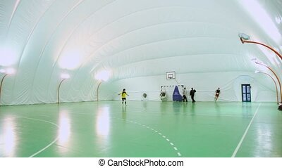 Four men play soccer on football field under cupola in...