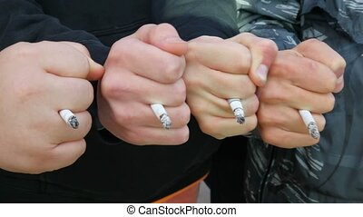 four men with their fists stuck between his fingers with...