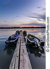 Four moored boats at sunset near a wooden pier. Vertical view of a pack of moored boats in a summer evening over sunset sky on background.