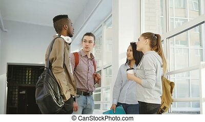 Four multi-ethnic studens are standing in big white spacious...