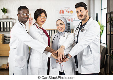 Group of four multicultural doctors in white lab coats stacking their hands together while standing at brigham hospital room. Successful international cooperation.