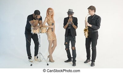 Four musicians perform a song in the studio with a white background. The African man sings very emotionally. A white man is playing the saxophone.