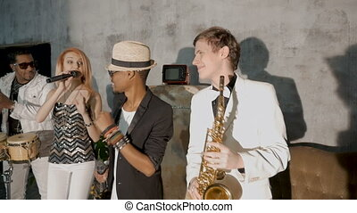 Four musicians perform in a nightclub. A beautiful white girl is dancing. A black man sings, one musician plays the saxophone, another black man plays the drums.