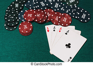 four of a kind of aces and chips on the green poker table