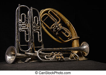 Four old brass instrument and horn stand on a table - Four...