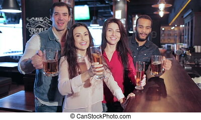 Four old friends at the bar with a glass of beer is welcomed new friends