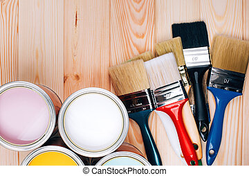 Four open cans of paint with brushes on natural wooden background.