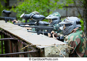 Four paintball players in camouflage and protective masks ...