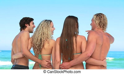 Four pals embrace each other at the beach