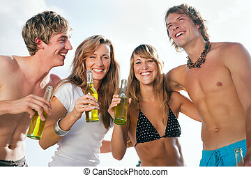 Four people celebrating beach party - Group of four very...