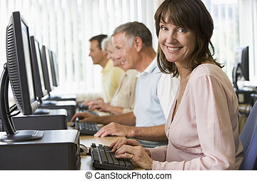 Four people sitting at computer terminals (depth of field/high key)