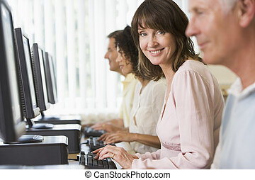 Four people sitting at computer terminals (selective focus/...