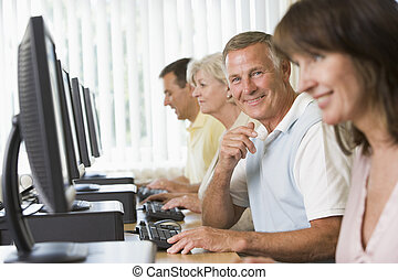 Four people sitting at computer terminals (selective focus/high key)