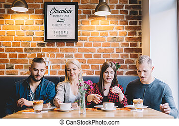 Four people sitting at the table in a cafe