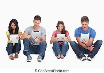 Four people sitting beside each other using their tablets