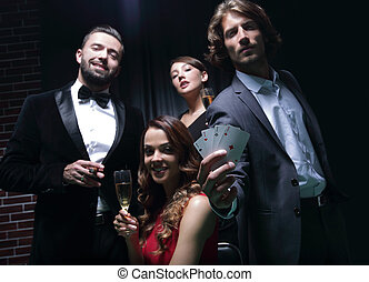 Four people toasting with champagne at roulette in casino
