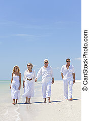 Four people, two seniors, couples or family generations, holding hands, having fun and walking on a tropical beach