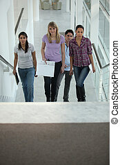 Four people walking up stairs