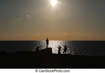 Four people watching sunset on beacch
