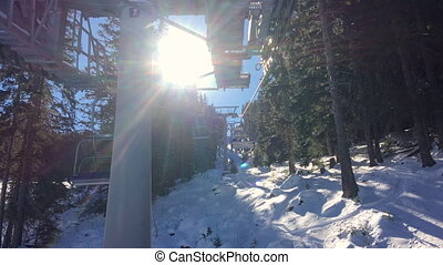 Four person ski chair lift going through the trees up a...