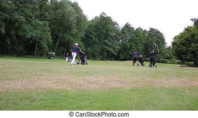 four persons pulling their caddies - four golf player...