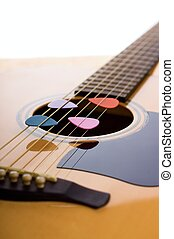Vertical photo of front side of acoustic guitar with bridge, strings and fretboard. Four colorful guitar picks are placed in strings over the hole in spruce board.