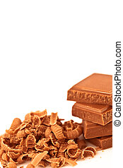 Four pieces of chocolate piled beside chocolate shavings
