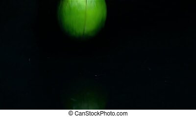 Four pieces of lime fall on the table in the water. Black background. Slow motion