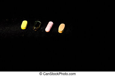 Four pills on dark background - pharmaceutical concept. Selective focus. Blurred view