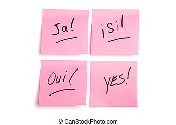 """Pink post it notes isolated on white with """"ja', """"si"""", """"oui"""", and """"yes"""" written"""