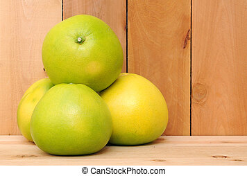 four pomelo on wooden background