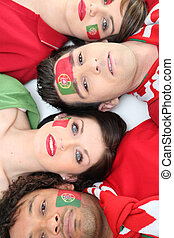 Four Portuguese soccer fans laying down together