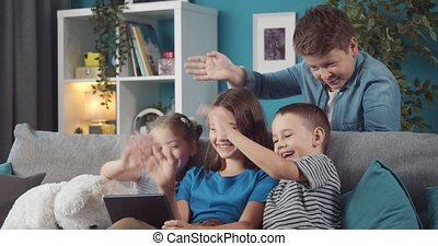 Four pretty kids waving during video chat on digital tablet