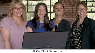 Four professional women smiling behind a computer in modern...