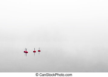 Four red buoys - Four red bouys in water on very foggy ...