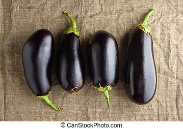 Four ripe black eggplants on linen cloth fabric. Rustic top view