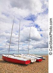 Four sailboats on a pebble beach