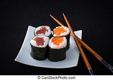 Four salmon, tuna maki sushi and chopstick on black, close ...