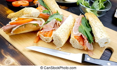 Four sandwiched on wooden board - Four sandwiched lying on...