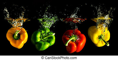 four several coloured paprika falling into water before ...