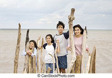 Four siblings by the lakeshore in summer, standing against dirftwood fencing
