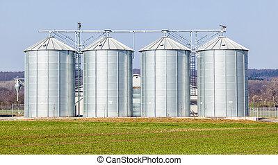 silver silos in field - four silver silos in field under...