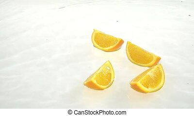 Four slices of orange fall into the water. White background. Slow motion