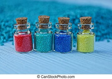 four small glass bottles with colored sand