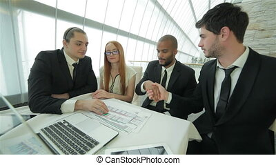 Four smiling successful businessmen sitting at table in office while discussing