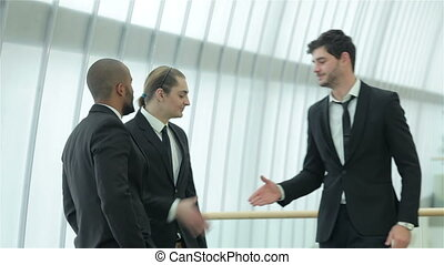 Four smiling successful businessmen shake hands with each other